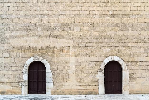 Hauts murs de pierre avec deux portes symétriques, fond de pierre médiévale.