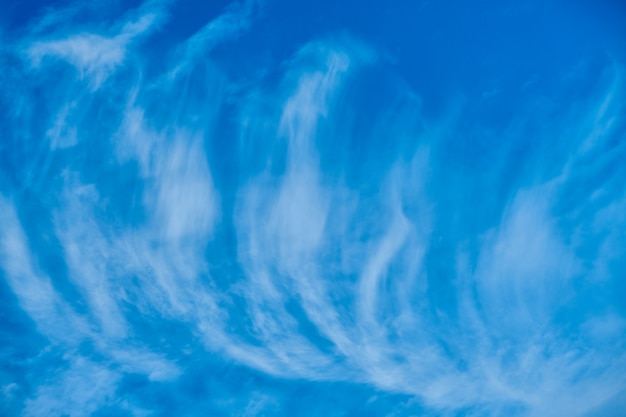 De hauts nuages blancs cirrus vaporeux en expansion par le vent pour couvrir le ciel bleu marine profond