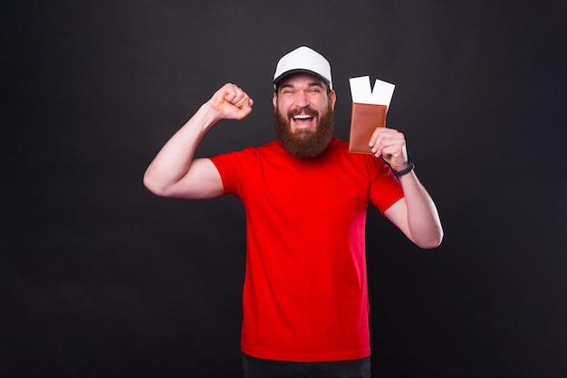 Hé, je suis libre de voyager dans le monde entier, joyeux bel homme barbu célébrant et tenant un passeport avec des billets