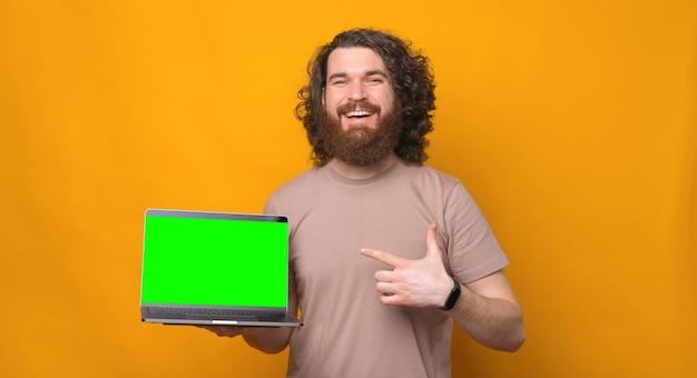 Hé regarde ça, joyeux homme barbu souriant aux cheveux bouclés pointant vers un ordinateur portable avec un écran vert