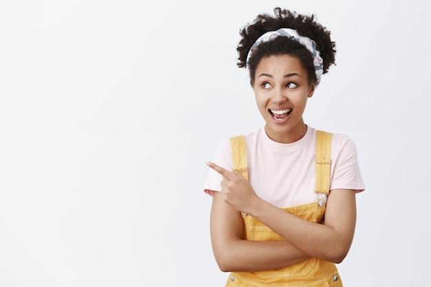 Hé regarde. intriguée et heureuse belle étudiante africaine aux cheveux bouclés en bandeau et salopette jaune, regardant et pointant vers la gauche avec un large sourire, posant une question sur un oiseau intéressant