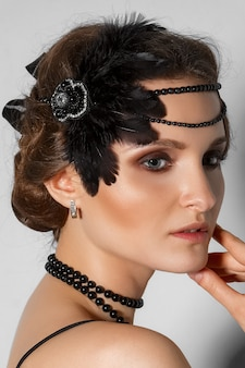 Head shot of model with plume in hair and black pearl bead in profile