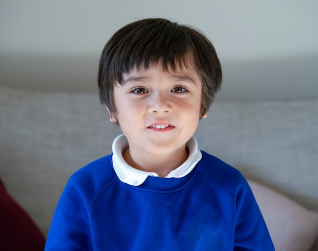 Head shot of school kid, portrait happy 6-7 ans childs with smiling face, candid shot mixed race healthy little boy relaxing at home. concept d'enfants positifs
