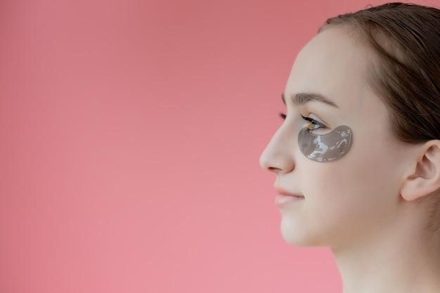 Head shot portrait close up smiling young woman avec masque hydratant sous les yeux à la recherche