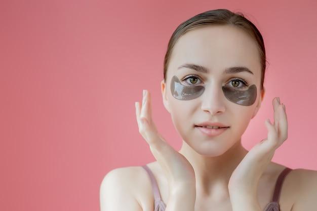 Head shot portrait close up smiling young woman avec masque de patchs hydratants sous les yeux regardant la caméra