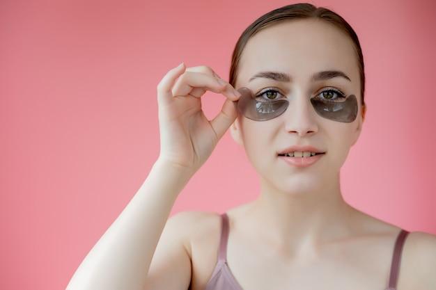 Head shot portrait close up smiling young woman avec masque de patchs hydratants sous les yeux