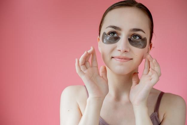 Head shot portrait close up smiling young woman with under eye hydratant patchs mask looking at camera bénéficiant d'une procédure de soins de la peau.