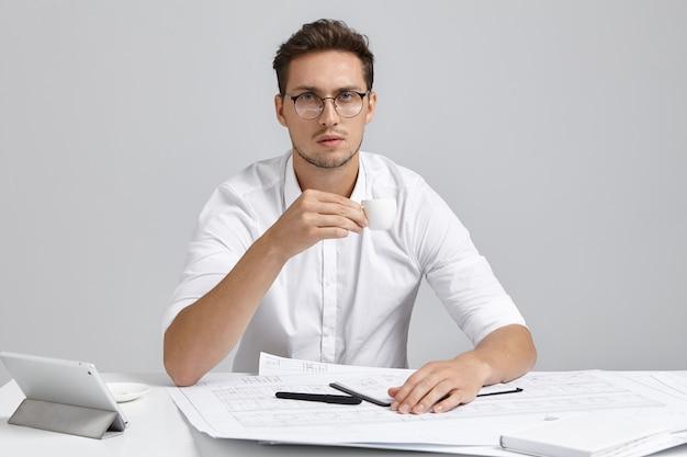 Headshotof attrayant jeune constructeur européen fatigué avec barbe tenant une tasse blanche, buvant un expresso tout en travaillant toute la nuit sur ordre urgent