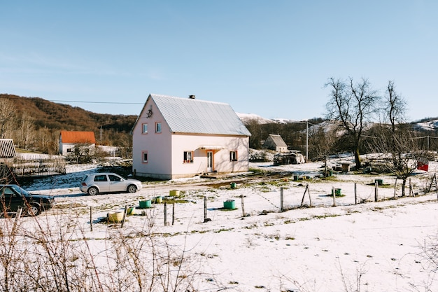 Hébergement privé dans une région vallonnée en hiver sur la neige avec des voitures en stationnement