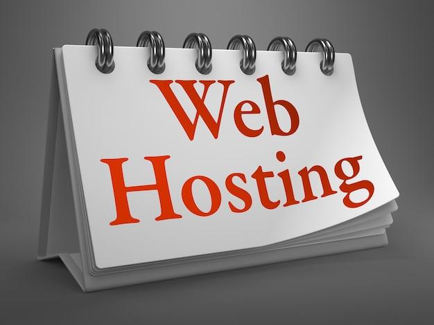 Hébergement web - mot rouge sur calendrier de bureau blanc isolé sur gris.