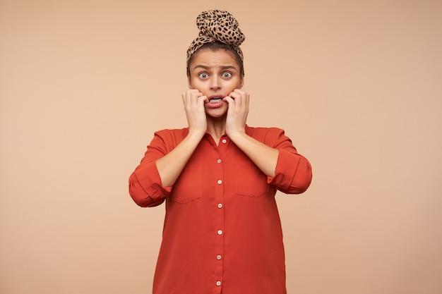 Hébété jeune belle femme aux cheveux bruns avec un maquillage naturel tenant son visage avec la main levée tout en regardant avec étonnement à l'avant, debout sur un mur beige