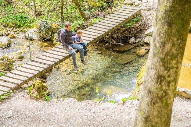 Héhé, assis sur un pont en bois au milieu de la forêt