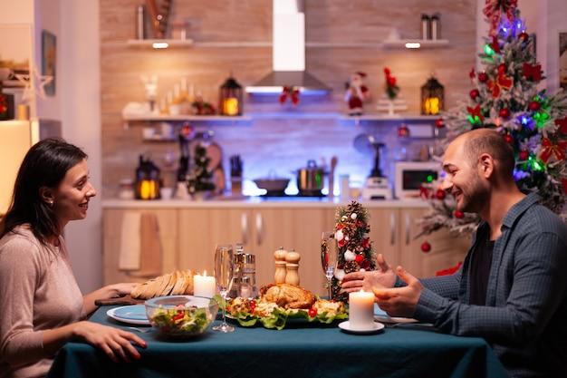 Héhé, assis à une table à manger romantique dans une cuisine décorée de noël