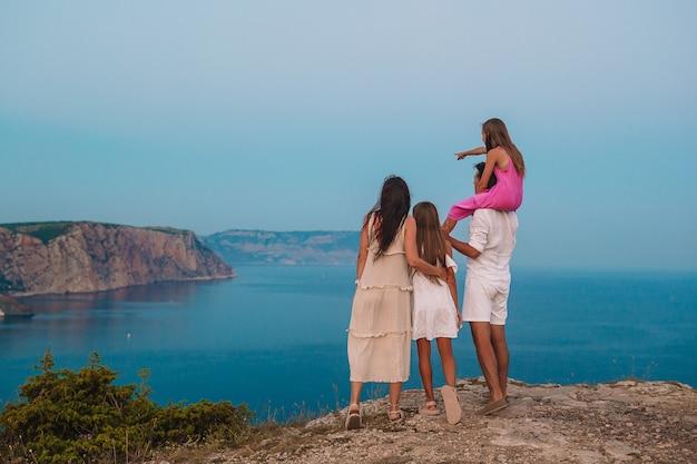 Héhé au bord de la falaise, profitez de la vue sur le rocher du sommet de la montagne au coucher du soleil