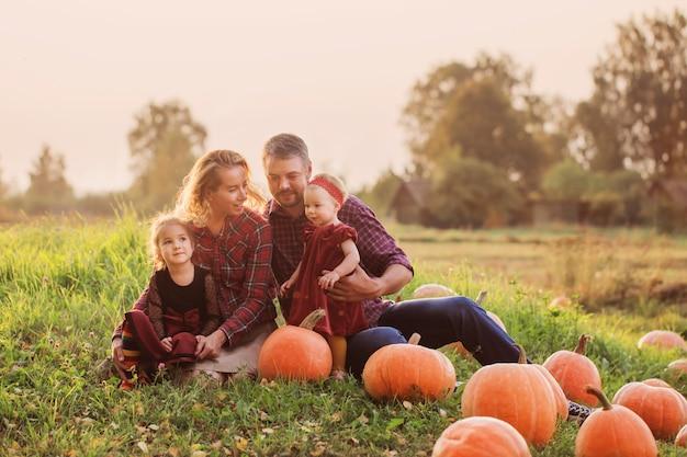 Héhé avec des citrouilles orange dans le champ d'automne