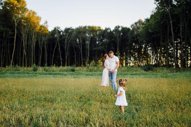 Héhé dans un parc en automne été. mère, père et bébé jouent dans la nature dans les rayons du coucher du soleil