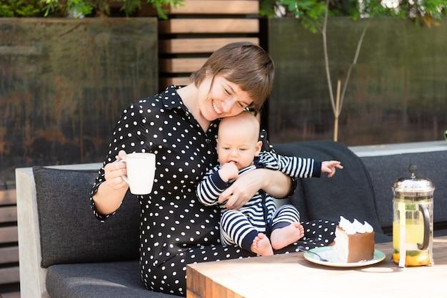 Héhé de deux, jeune femme avec son mignon petit fils, se détendre ensemble en été café en plein air mère et enfant, concept parental