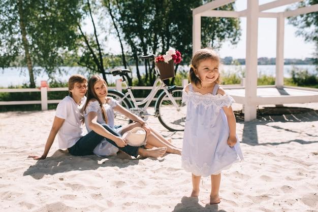 Héhé à l'extérieur passer du temps ensemble. père, mère et fille s'amusent et jouent sur une plage