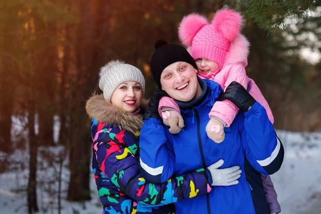 Héhé, jeune couple et leur fille passer du temps en plein air en hiver