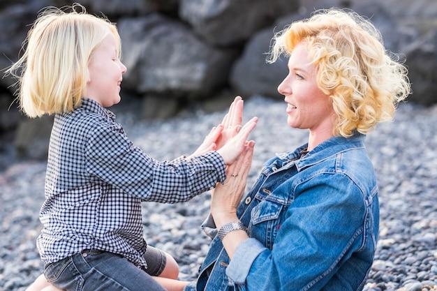 Héhé, jeune mère blonde et gentil fils joyeux jouant ensemble