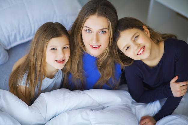 Héhé, jouant à la maison. filles de mère et enfant en bas âge se détendre et s'amuser au lit dans la matinée de week-end