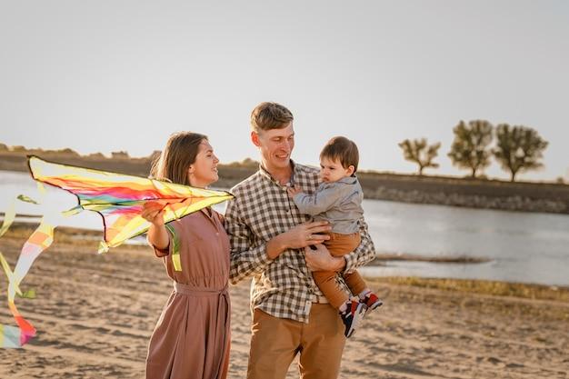 Héhé, marchant sur la plage de sable. père, mère tenant son bébé sur les mains et jouant avec le cerf-volant.