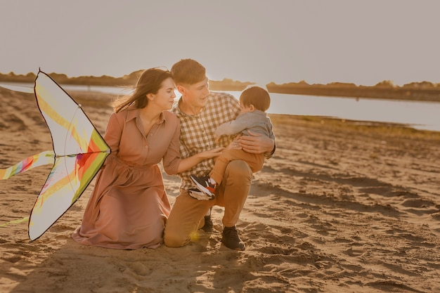 Héhé marchant sur la plage de sable de la rivière. père, mère tenant son bébé sur les mains et jouant avec un cerf-volant.