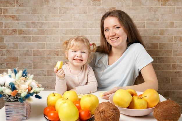 Héhé, mère et enfant, fille de bébé avec des fruits alimentaires sains sur la cuisine intérieure