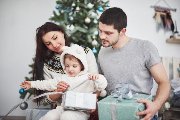 Héhé à noël dans la matinée, ouverture de cadeaux ensemble près du sapin. le concept de bonheur et de bien-être familial