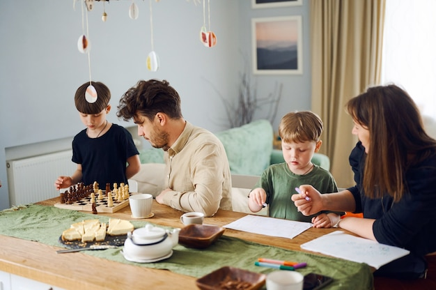 Héhé, passer du temps ensemble à la maison, père jouer aux échecs avec son fils, mère dessinant avec enfant à la maison