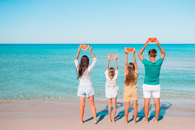 Héhé avec pastèque sur la plage. les parents et les enfants au bord de la mer s'amusent.