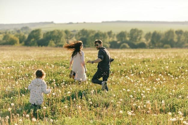 Héhé, père de famille, mère et enfant fille sur la nature au coucher du soleil