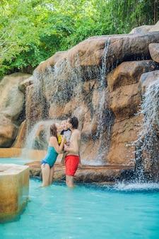 Héhé, relaxant sous une cascade dans un parc aquatique