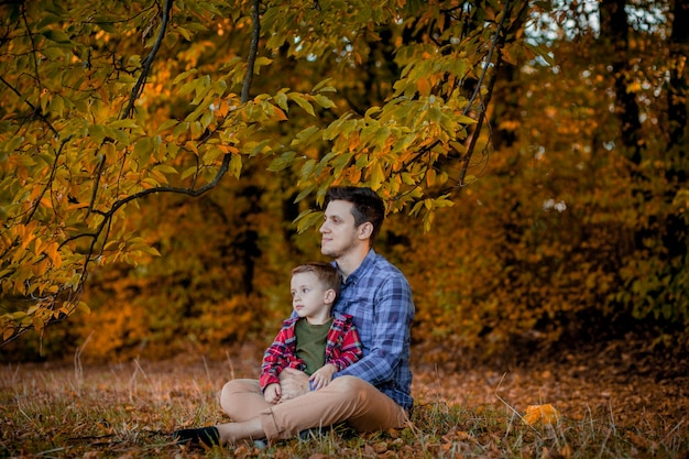 Héhé, s'amuser en plein air dans le parc de l'automne. père et fils contre les feuilles floues jaunes