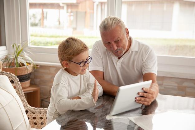 Héhé, senior et petit garçon à l'aide de tablette pour une conversation avec leurs parents ou amis
