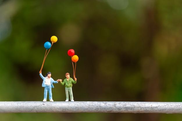 Héhé, tenant des ballons colorés
