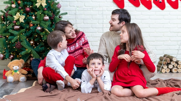 Héhé en tenue de noël sur le sol près de l'arbre de noël à la maison. bonne idée de famille