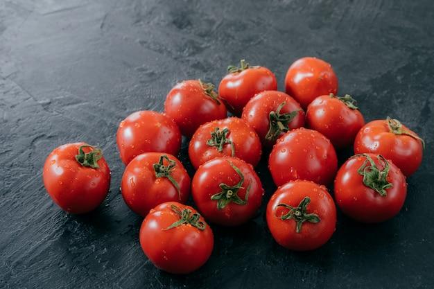 Heilroom tomates rouges fraîches avec des feuilles vertes, gouttes d'eau, isolés sur fond sombre. délicieux légumes mûrs du jardin