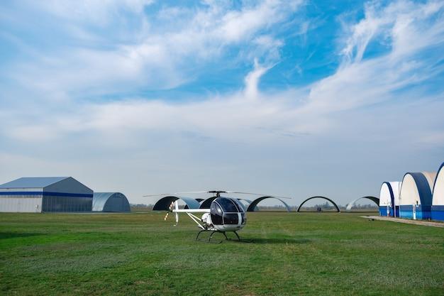 Hélicoptère blanc ultraléger sur terrain de vol vert en aéroclub