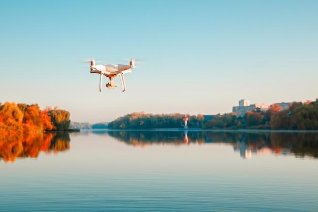 Hélicoptère de drone avec appareil photo numérique survolant un lac