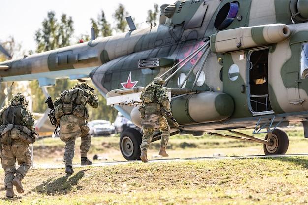 Hélicoptère militaire debout sur le sol et des soldats s'y chargeant.