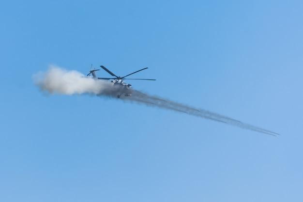 Hélicoptère militaire fait un tir avec une volée de plusieurs missiles avec de la fumée.