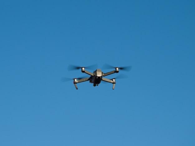 Hélicoptère quadrirotor ou quadrirotor volant haut sur fond de ciel bleu