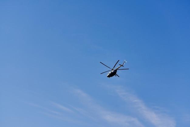 Hélicoptère volant sur fond de nuages et de ciel bleu
