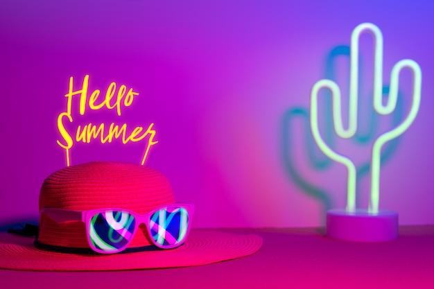 Hello summer avec chapeau et lunettes de soleil refection néon avec cactus sur rose et bleu sur table