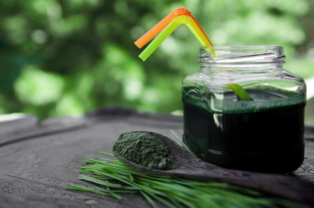 Herbe de blé frais boire en pot et pousses en poudre dans la cuillère sur la table de jardin.