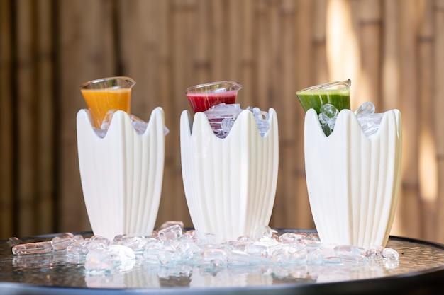 Herbe multiple et mélangée avec du jus de fruits à la boisson de couleur rouge vert et orange dans un petit bocal en verre décoré de glace autour.