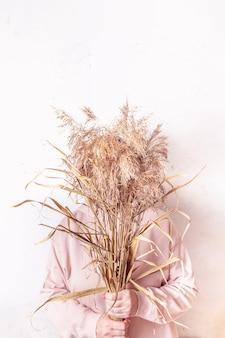 L'herbe de la pampa dans les mains de la femme. cortaderia selloana. femme sans visage en robe rose contre résumé
