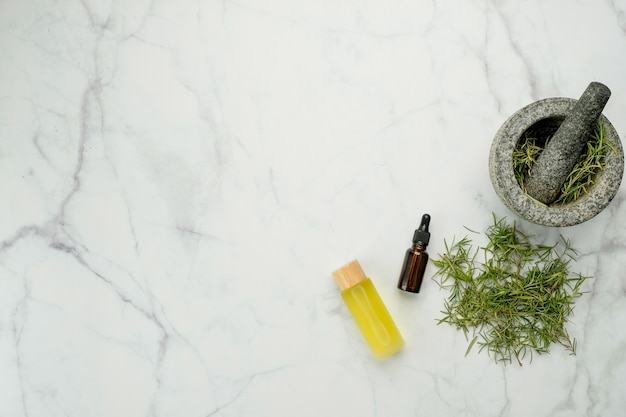 Herbe de romarin et huiles essentielles sur la vue de dessus de table en marbre