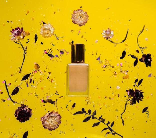 Herbe sèche bellis avec bouteille de fondation sur fond jaune isolé. sans ombres